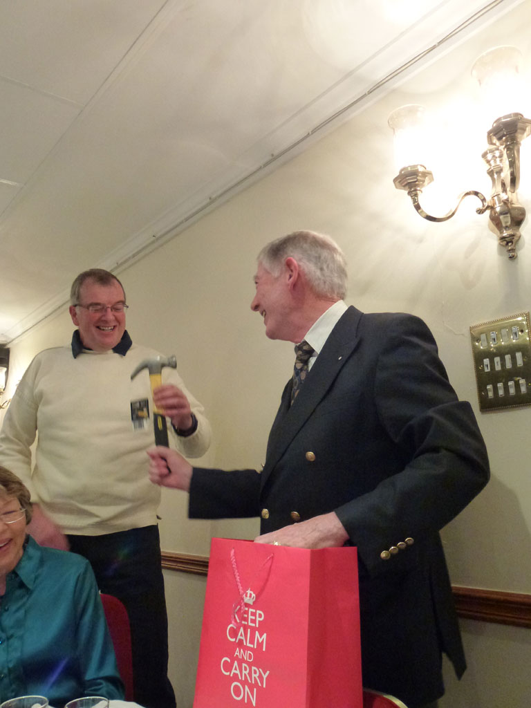 Mr Matthews presents the club's 'Master Builder' with a new hammer (and a bottle of whisky) for his efforts